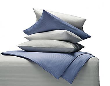 Bettzubehör unter anderem Kissen, Bettzeug, Bettdecken, Bettwäsche, Spannbettlaken und Matrazenschoner